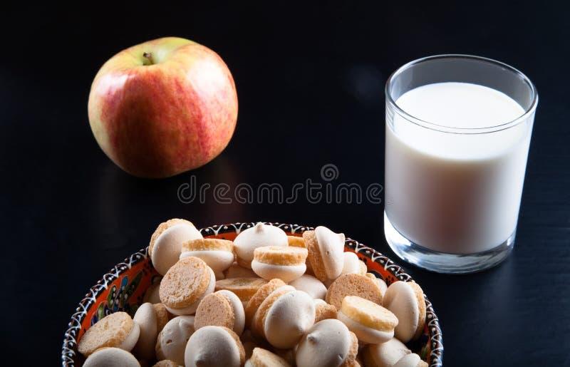 Små kakor i den turkiska bunken, äpplet och exponeringsglaset av mjölkar på a royaltyfri bild