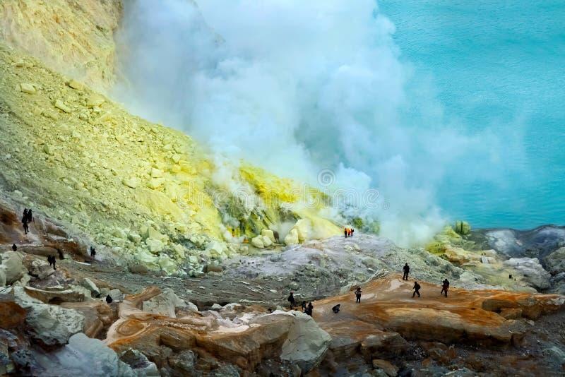 Små konturer av folk i krater av den Ijen vulkan mot bakgrunden av gult svavel- vaggar och ett sulphurous blått royaltyfri bild