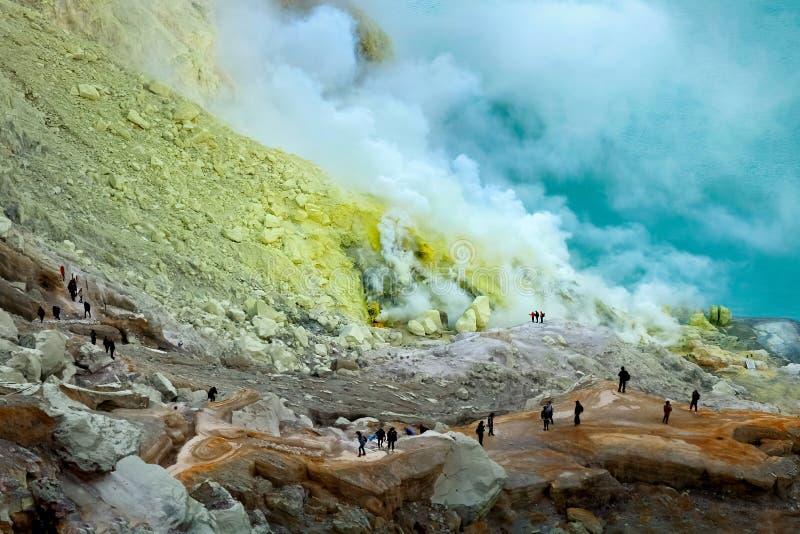 Små konturer av folk i krater av den Ijen vulkan mot bakgrunden av gult svavel- vaggar och ett sulphurous blått arkivbilder
