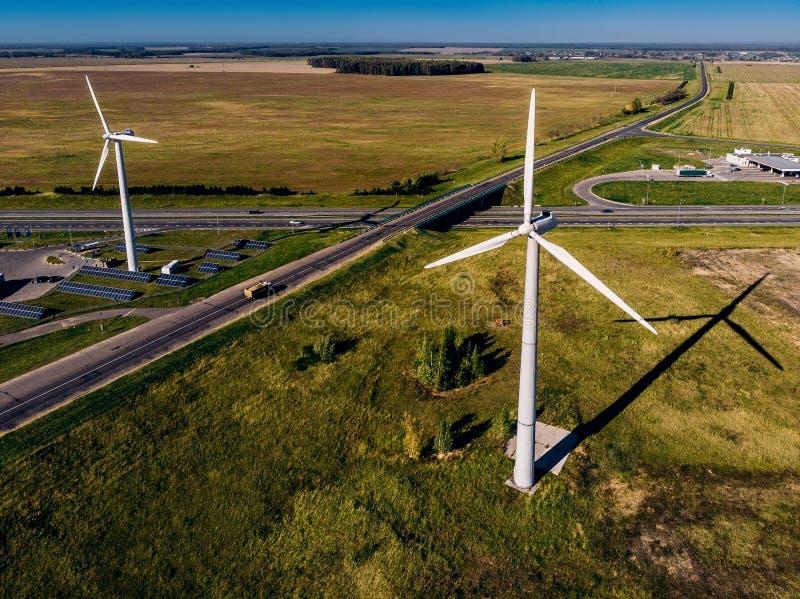 Små lastbilritter på den stora vägen och enorm bakgrund för himmel för vindturbiner som blå klar frambringar elektricitet längs arkivbild