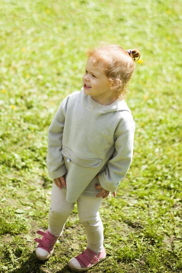 Små lyckliga rödhåriga flickakörningar på det gröna gräset och värmer upp i sommarsolen i barnen parkerar royaltyfri bild