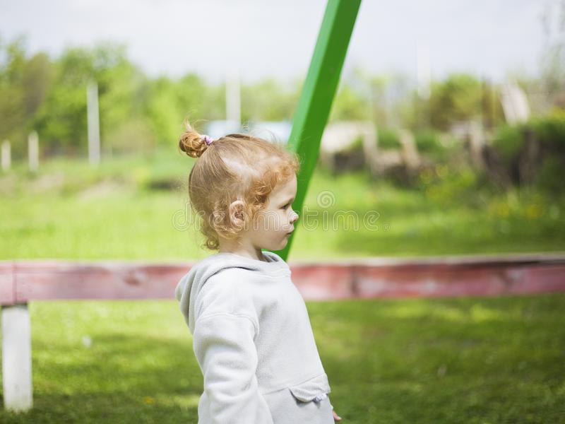 Små lyckliga rödhåriga flickakörningar på klippt grönt gräs i barn parkerar under den angenäma solen arkivfoton