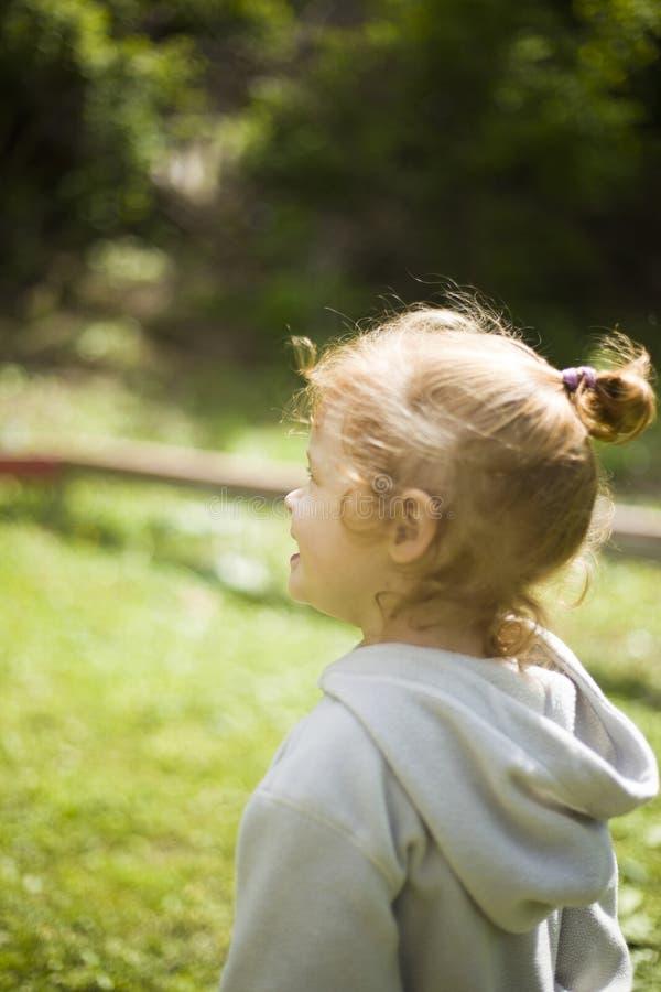 Små lyckliga rödhåriga flickakörningar på klippt grönt gräs i barn parkerar under den angenäma solen royaltyfri fotografi