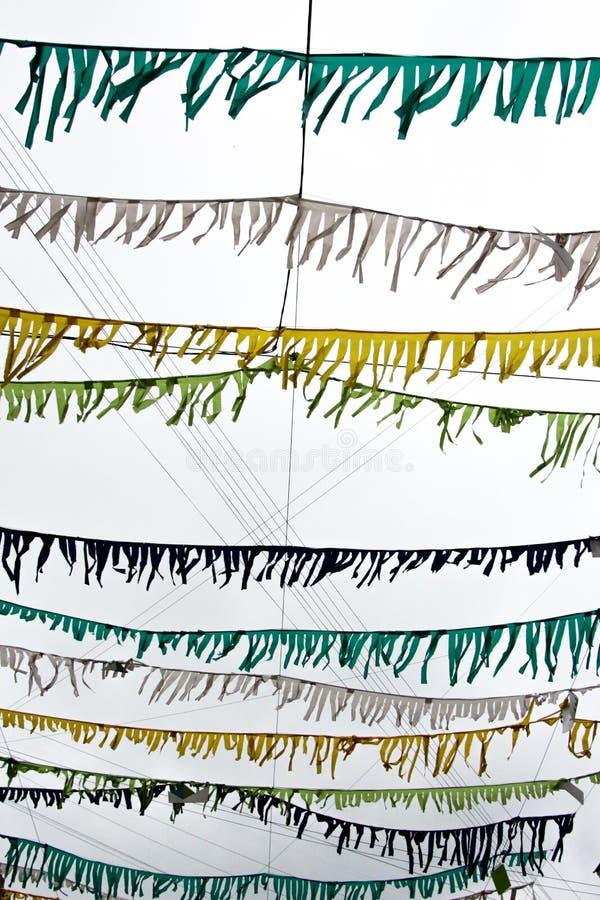 Små mångfärgade flaggor fästas till tråden och hänger mot bakgrunden av himlen som har fördunklats royaltyfri foto