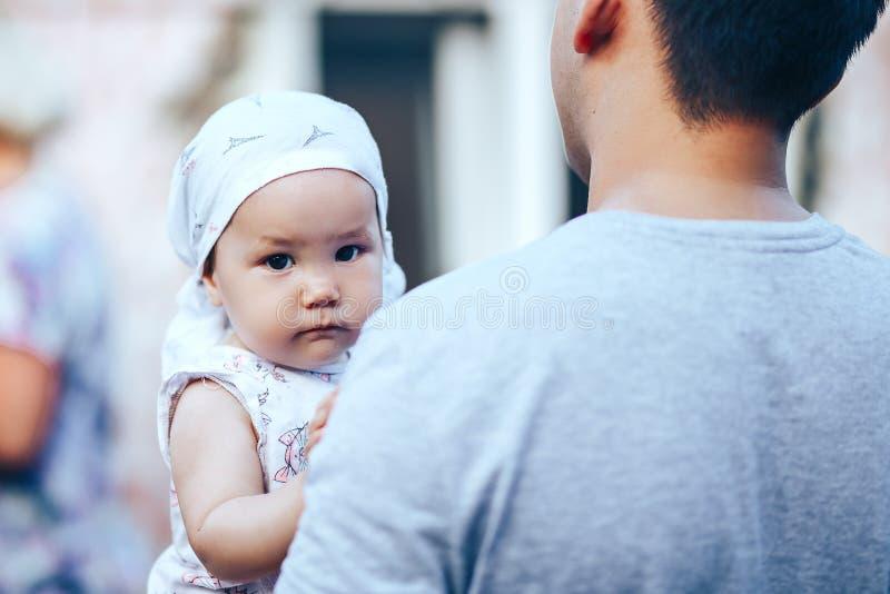 Små mörker-haired behandla som ett barn flickan på utomhus- faderhänder och att se kameran royaltyfri fotografi