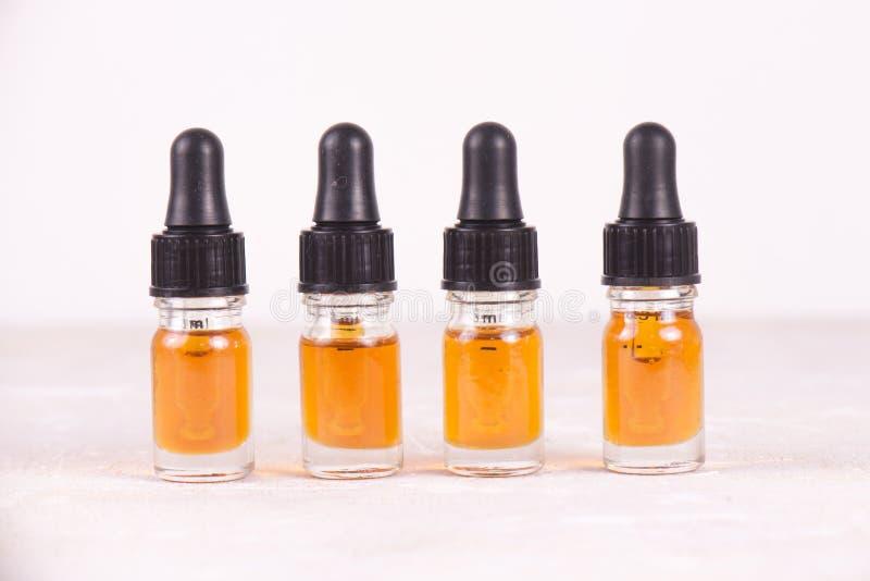 Små medicinflaskor av CBD-olja, cannabis bor kådaextraktion som isoleras på whi royaltyfri foto