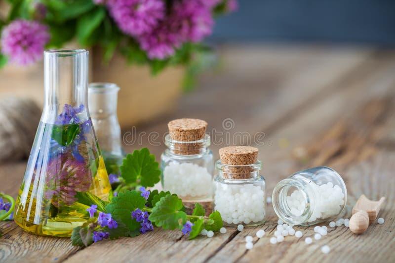 Små medicinflaskor av tinktur av sunda örter och flaskor av homeopatismå kulor royaltyfri fotografi