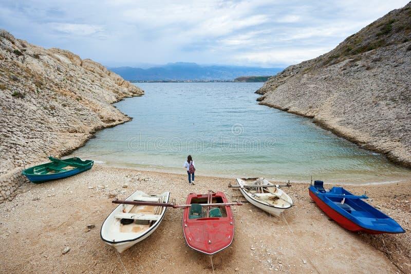 Små motorfartyg på hemtrevlig hamnkust bland höga steniga kuster och ung turist- kvinna royaltyfri foto