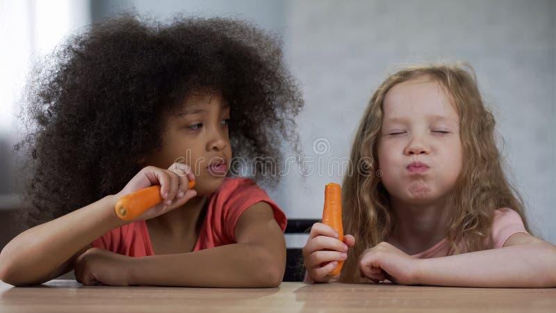 Små nätta blandras- flickor som sitter på tabellen och äter moroten med aptit royaltyfri fotografi