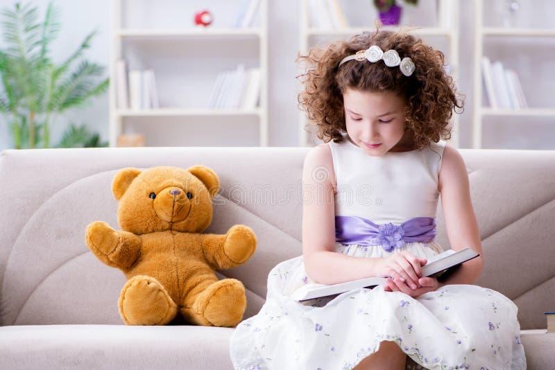 Små nätta flickaläseböcker hemma royaltyfri foto