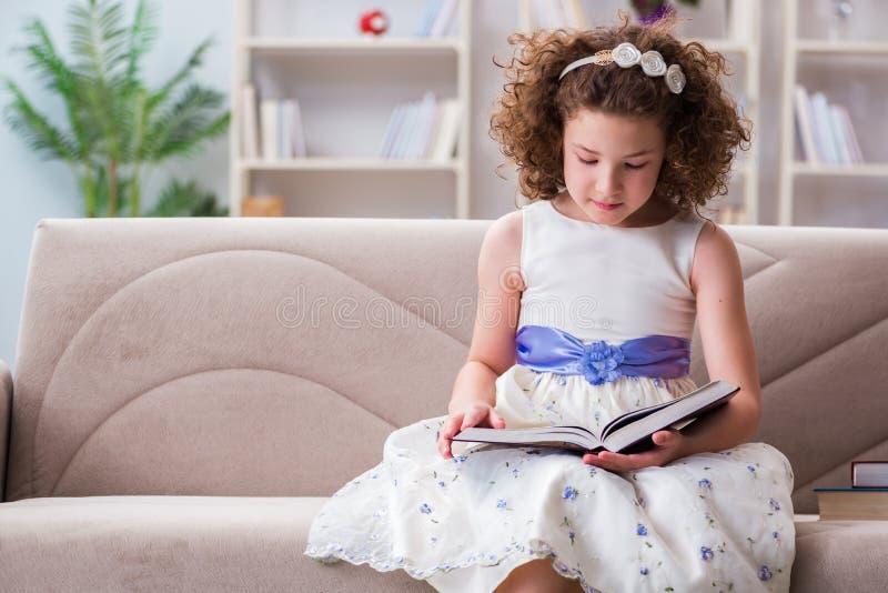 Små nätta flickaläseböcker hemma arkivbild