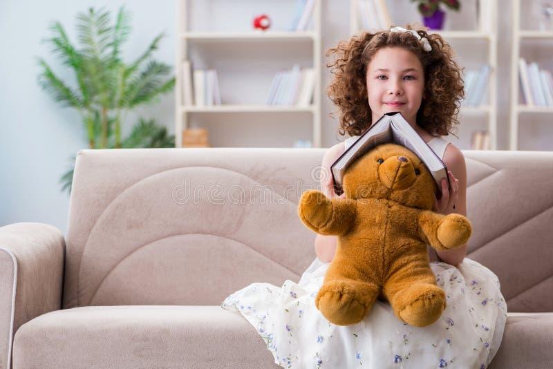 Små nätta flickaläseböcker hemma royaltyfri fotografi