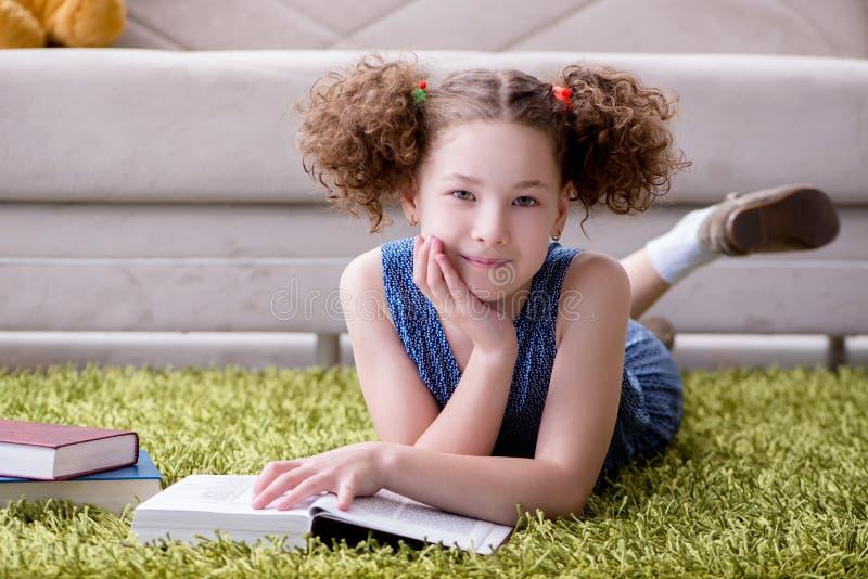 Små nätta flickaläseböcker hemma arkivbilder