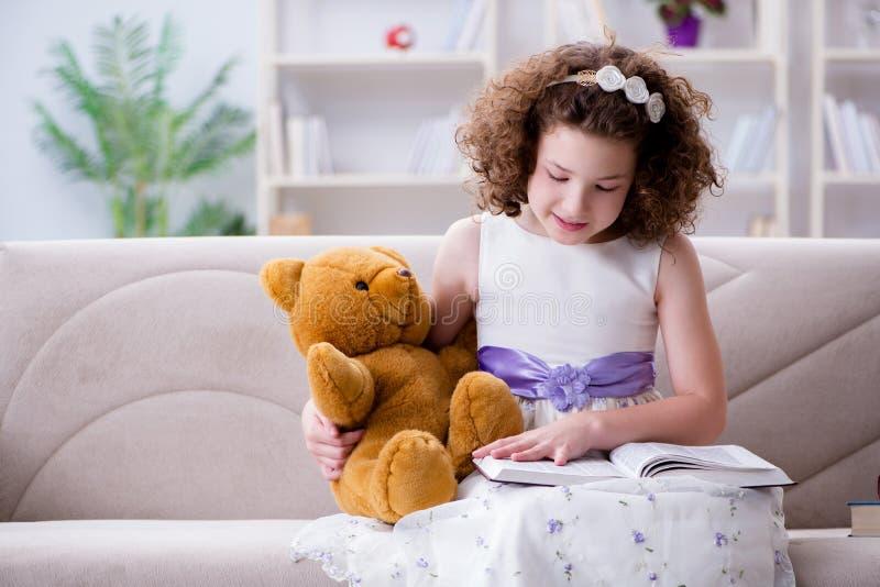 Små nätta flickaläseböcker hemma royaltyfria bilder