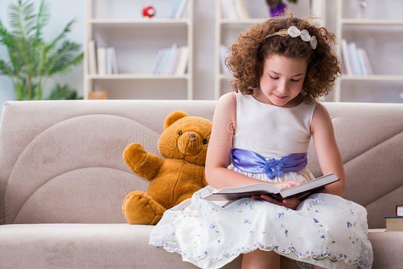 Små nätta flickaläseböcker hemma arkivfoton