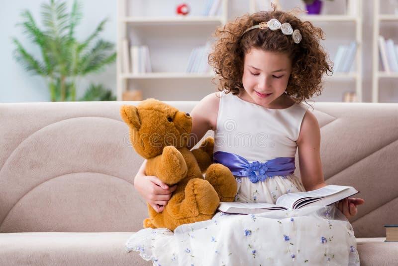 Små nätta flickaläseböcker hemma arkivfoto