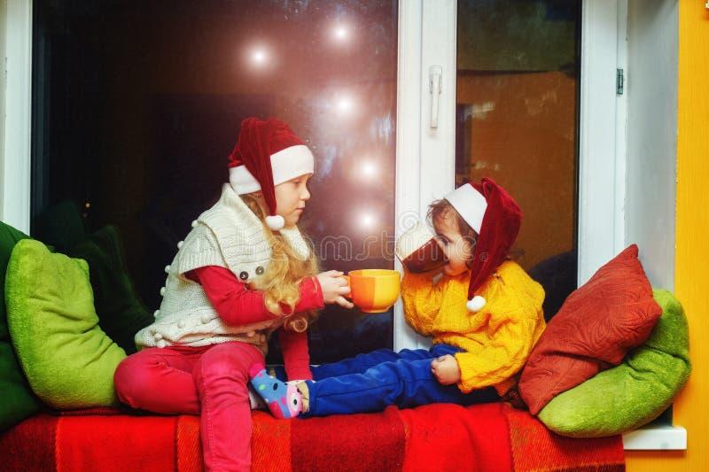 Små nätta flickor i jultomten julhattar i huset arkivfoton