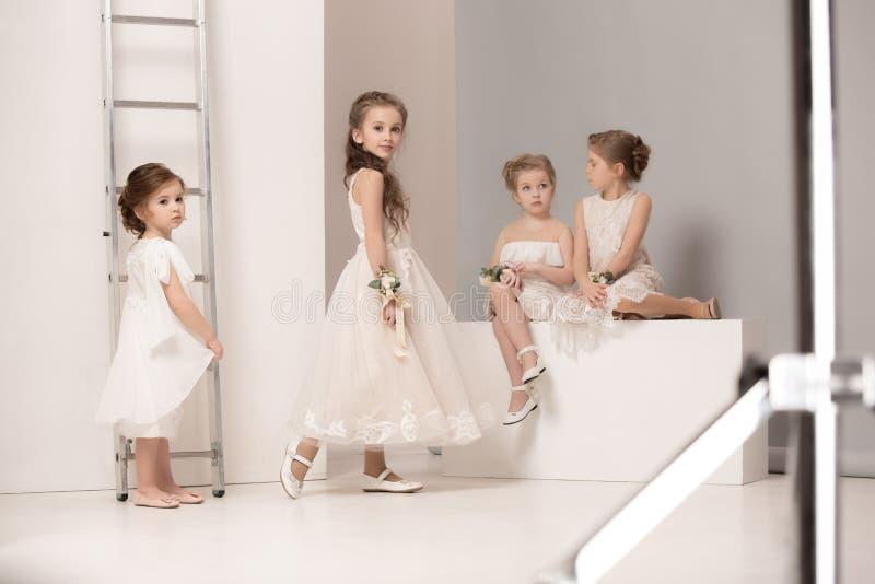Små nätta flickor med iklädda bröllopsklänningar för blommor royaltyfria bilder