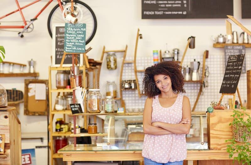 Små och medelstora företagägare som proudly står i hennes coffee shop arkivbilder