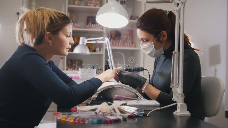 Små och medelstora företag - manikyrist - spika förlagen i den medicinska maskeringen som gör yrkesmässig manikyr arkivbilder