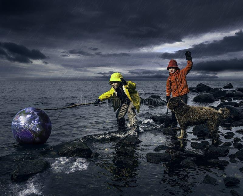 Små pojkar som sparar ett jordklot fotografering för bildbyråer