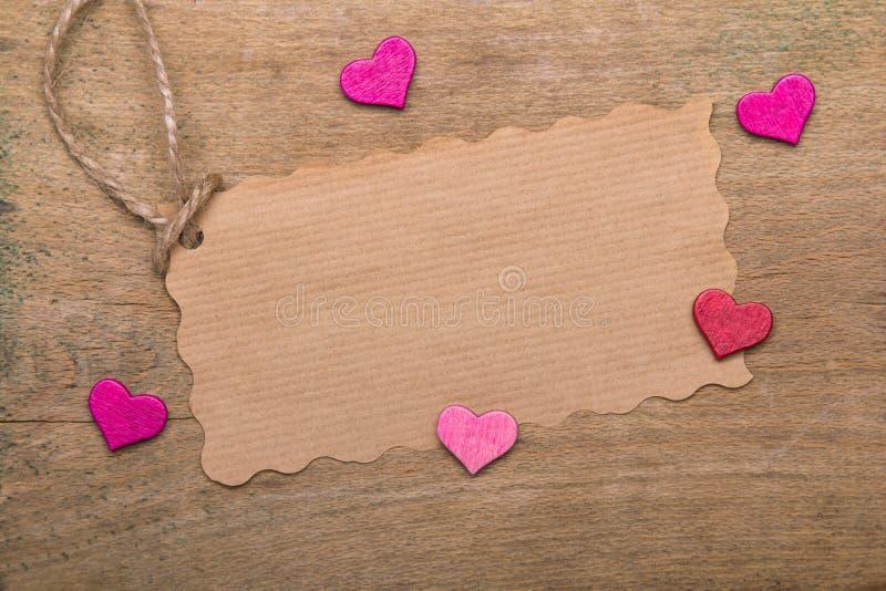 Små rosa hjärtor och tomt pappers- kort på träbakgrund royaltyfri fotografi