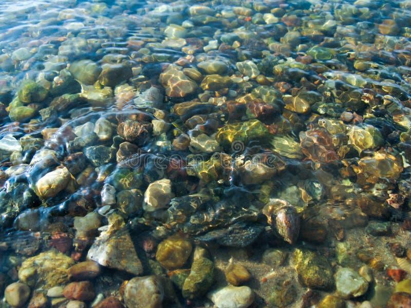 Små runda stenar under klart klart vatten royaltyfri bild