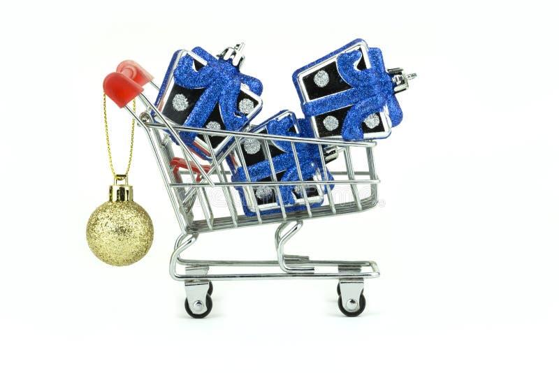 Små silvergåvaaskar i liten shoppa vagn med den guld- skinande bollen för festival som isoleras med urklippbanan på vit bakgrund arkivfoton