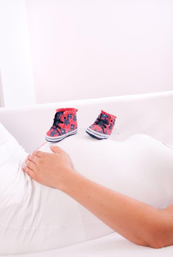 Små skor för det ofött behandla som ett barn i buken av gravida kvinnan arkivbild
