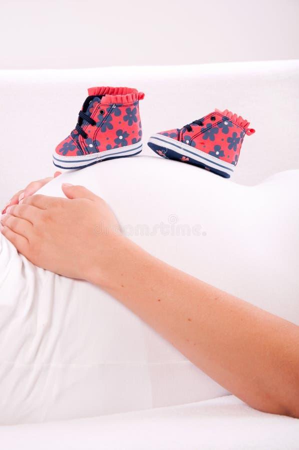 Små skor för det ofött behandla som ett barn på buken av gravida kvinnan arkivbild