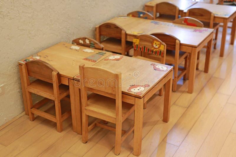 Små skrivbord och stolar för unge i studentklassrum royaltyfri bild