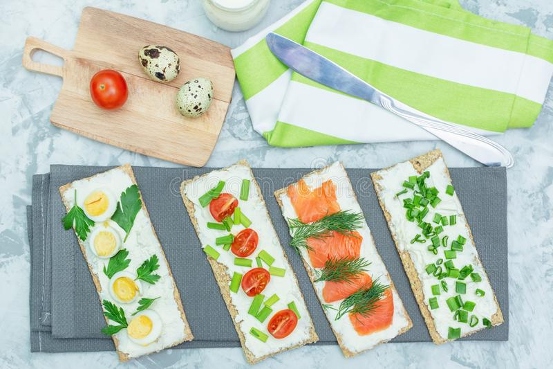 Små smörgåsar med den ostmassaost, tomater och forellen Ett ljust sommarmellanmål lagas mat på en grå tabell Foto ?ver arkivbild
