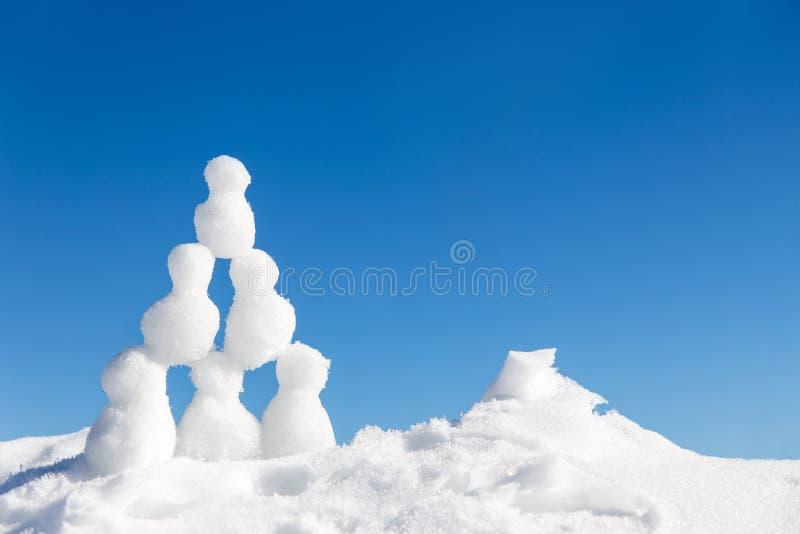 Små snögubbear figurerar byggande av en pyramide i snön fotografering för bildbyråer
