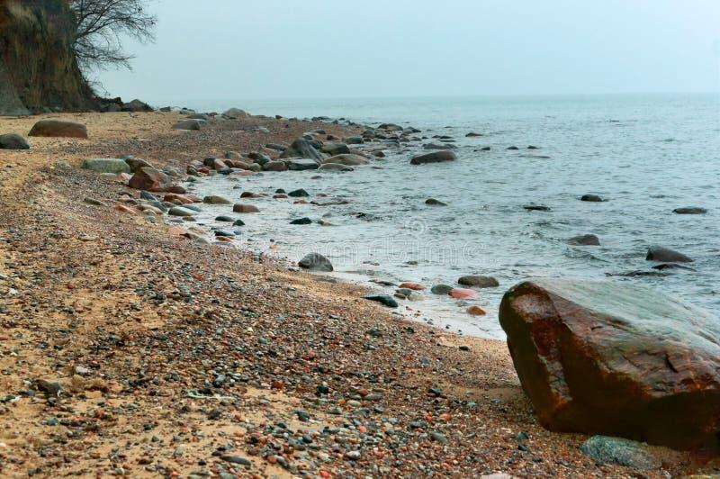 Små stenar på kusten, låga vågor kör in i havskusten, havet vinkar på stranden, en storm i det baltiska havet arkivfoto