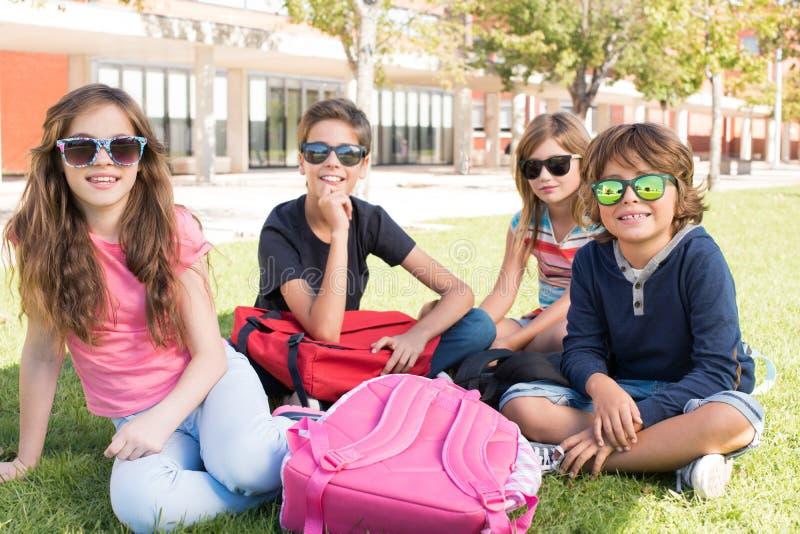 Små studenter på skolauniversitetsområdet arkivfoton