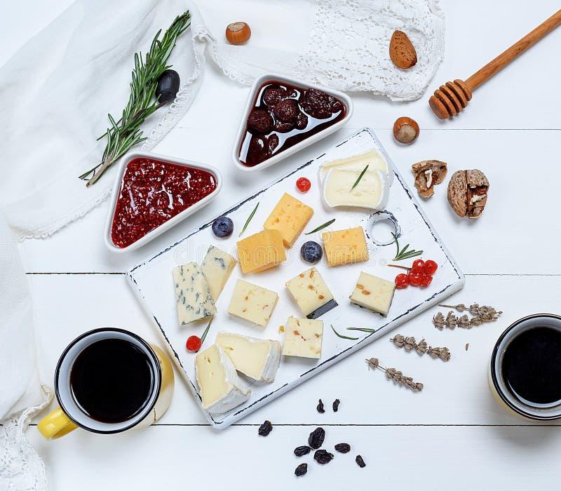 Små stycken av brieost, roquefort, camembert, cheddar och ost med valnötter royaltyfri bild