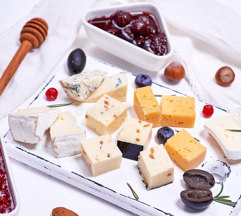Små stycken av brieost, roquefort, camembert, cheddar och ost med valnötter på ett vitt träbräde royaltyfria foton