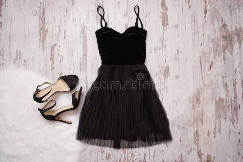 Små svarta klänning- och svartskor Träbakgrund, trendigt begrepp royaltyfri fotografi