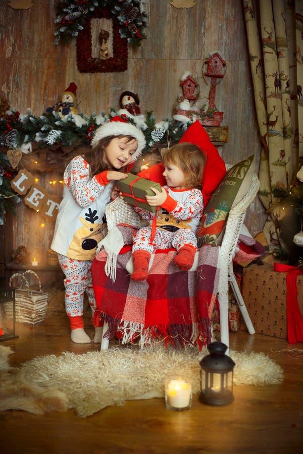 Små systrar i pyjamas på julaftonen arkivbilder