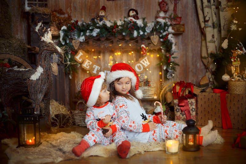 Små systrar i pyjamas på julaftonen fotografering för bildbyråer