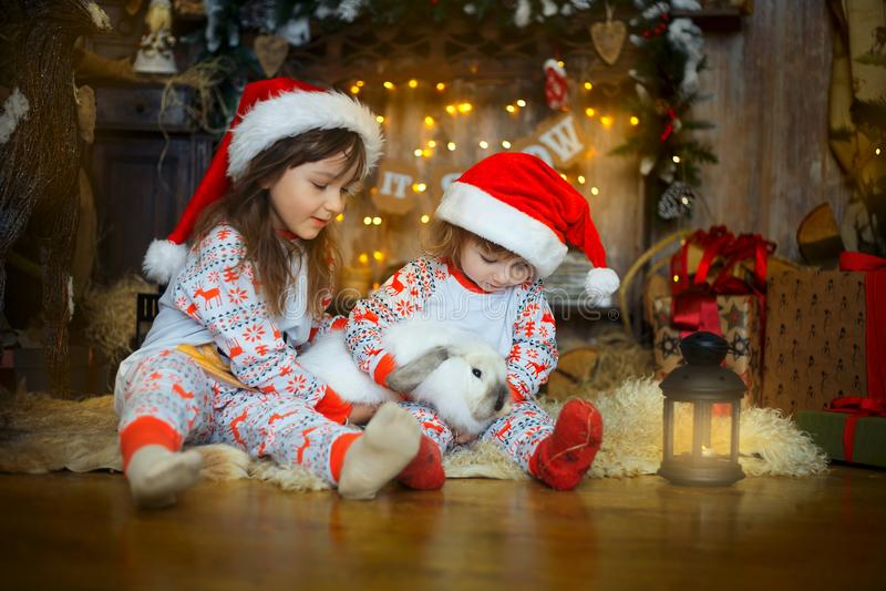 Små systrar i pyjamas på julaftonen royaltyfri fotografi