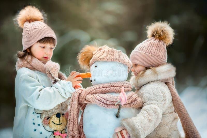 Små systrar med snögubben arkivfoto