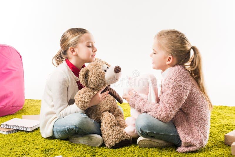 små systrar som spelar med mjuka leksaker, medan sitta på golv arkivbilder