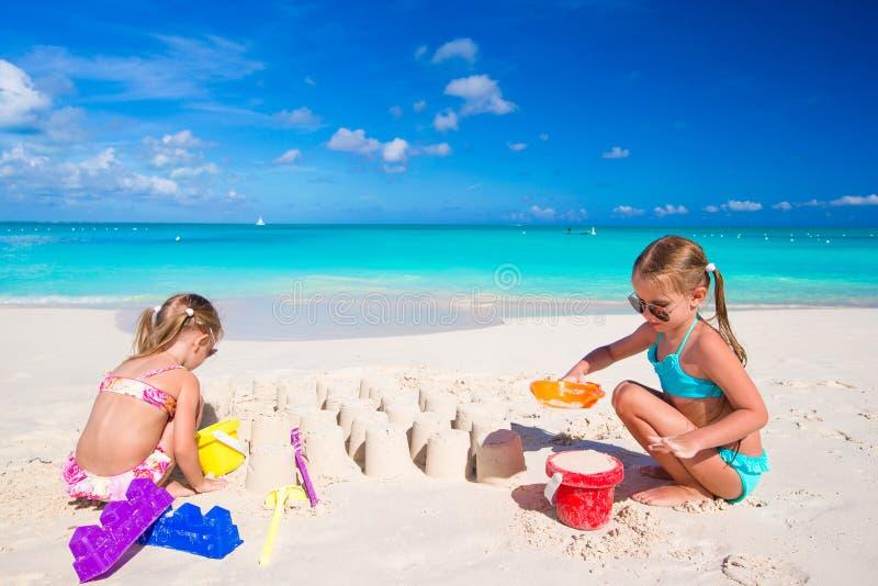 Små systrar som spelar med strandleksaker under arkivfoton