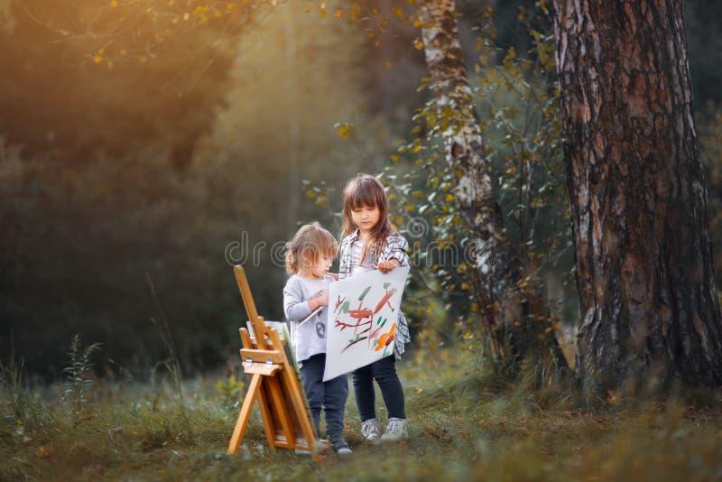 Små systrar som utomhus målar royaltyfri bild