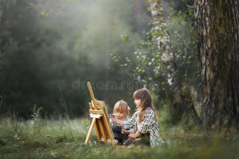 Små systrar som utomhus målar arkivbild