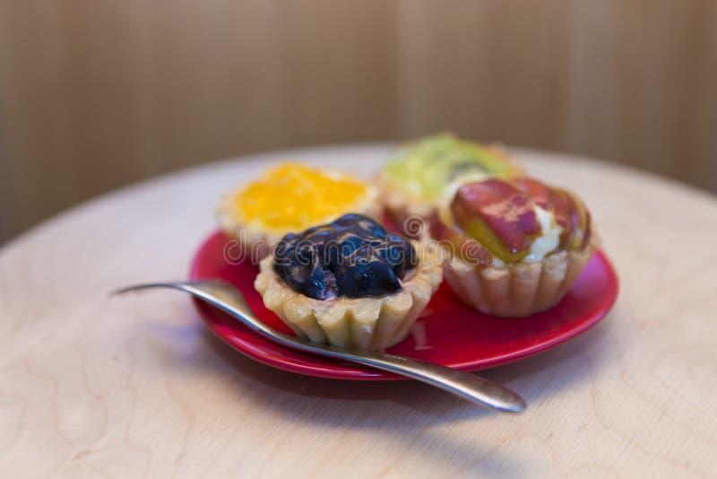 Små tarts för körsbär, för kiwi och för ananas arkivbilder