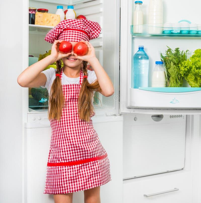 Små tomater för kockflickaholdin som ögon arkivbilder