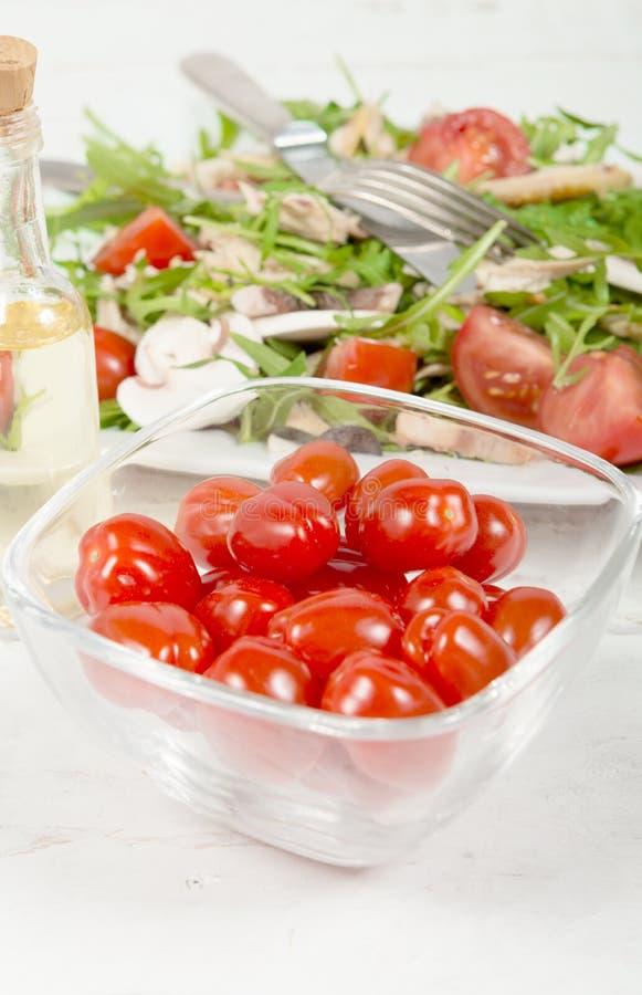 Små tomater i en glass krus med sallad royaltyfria bilder