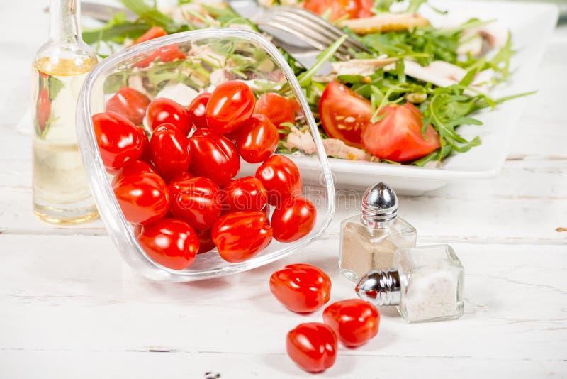 Små tomater i en glass krus med sallad arkivbild